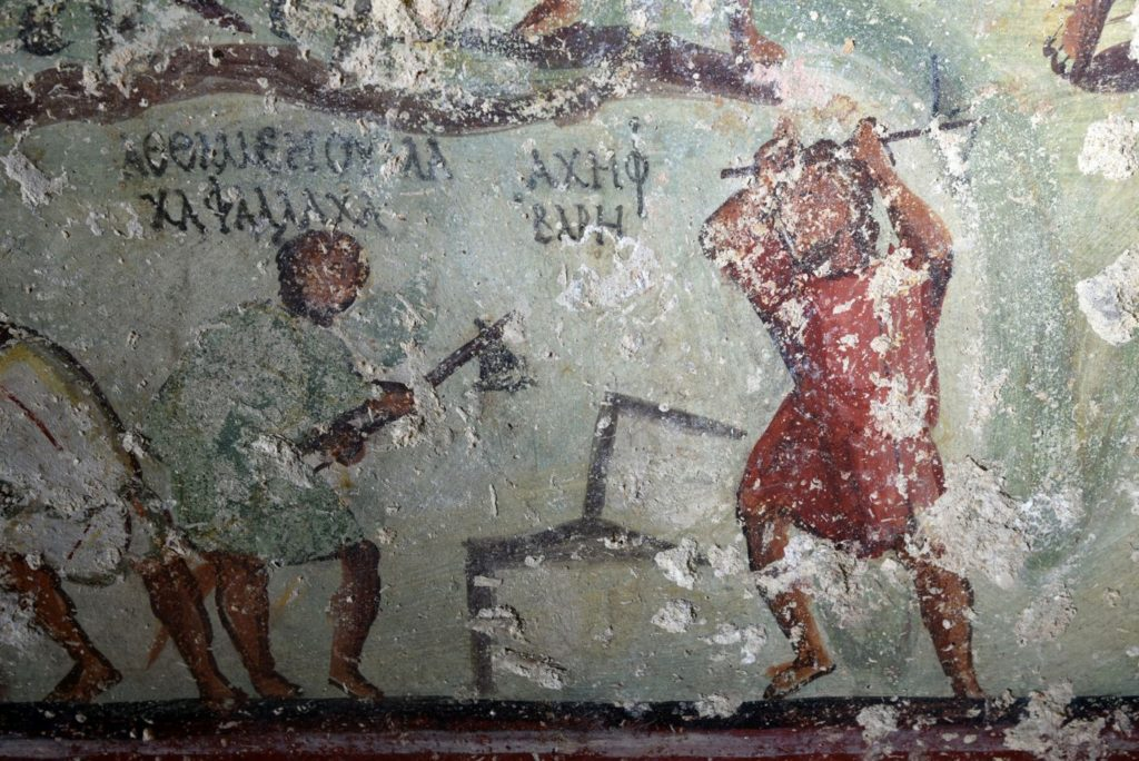 A mural of stonecutters at work is accompanied by rudimentary speech bubbles written in Aramaic using Greek letters, decorating a tomb in Capitolias