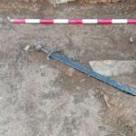 The sword was discovered under a mortar floor in a large room with a hearth and a work bench.