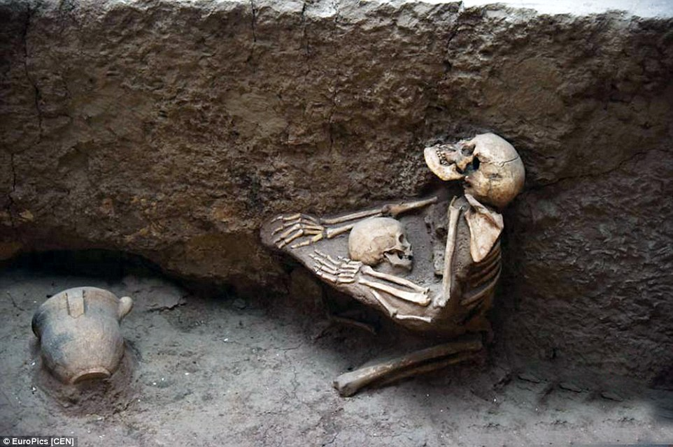 Skeletal remains show the mother kneeling down on the ground with her arms around her son in central China