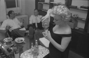 In her New York apartment, Marilyn Monroe pours a drink from a decanter as her then-husband, playwright Arthur Miller, sits in the background.