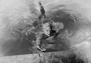 Marilyn Monroe, playing Ellen Arden, swims naked in Something's Got to Give. The movie was never completed due to Monroe's sudden death during production.