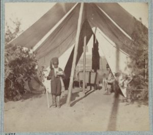 Photograph shows young African American camp servant of Colonel Lloyd Aspinwall of Field & Staff, 22nd New York Infantry Regiment, standing in front of tent with a sword as Aspinwall peeks from inside the tent.