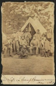 Photograph shows uniformed soldiers with guns posed in front of a tent; an African American child sits in front of the group.