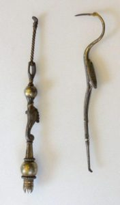 Two toiletry items, one in the shape of a crane-like bird; the other with an empty socket, probably for bristles for a makeup brush.