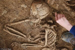 An Anglo-Saxon woman is carefully excavated from a fifth and sixth century burial ground in Oakington