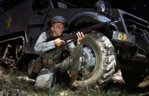 Infantryman wearing Brodie helmet, kneeling in front of M3 Half-track, holds an M1 Garand rifle. Fort Knox, June 1942