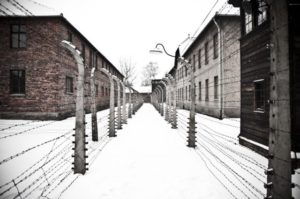 """The Auschwitz concentration camp is located about 30 miles (50 km) from Krakow. The picture shows two rows of electrical barbed wire surrounding the camp on winter day."""""""