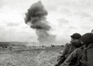 U.S. soldiers protect themselves from enemy fire as an 88 mm shell explodes on Utah Beach.