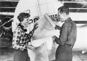 Pilot Amelia Earhart and her navigator, Fred Noonan, with a map of the Pacific that shows the planned route of their last flight