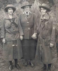 Juliette Gordon Low (center) standing with two Girl Scouts, Robertine McClendon (left) and Helen Ross (right)