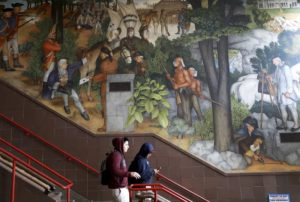 In this photo taken April 3, 2019, a pair of students walk past a historic mural that includes slaves and a dead Native American at George Washington High School in San Francisco. The San Fransisco school board unanimously voted Tuesday, June 25, 2019, to destroy a controversial mural displayed in a public high school.