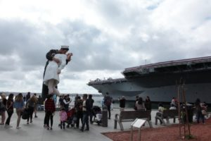 San Diego, California USA – May 27, 2018: Tourists visit Unconditional Surrender Statues and USS Midway Museum in San Diego, California