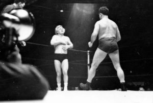 A wrestler strides toward Gorgeous George who stands near a corner of the ring with his hands on his chest where he had received a blow in the previous maneuver in the wrestling match. Photography by S. Kubrick.