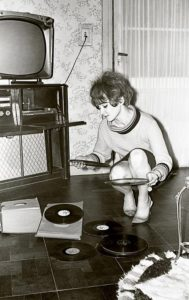 Vintage black and white photo from the sixties of a young woman looking at vinyl records.