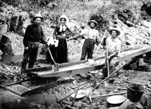 A woman with three men panning for gold during the California Gold Rush.