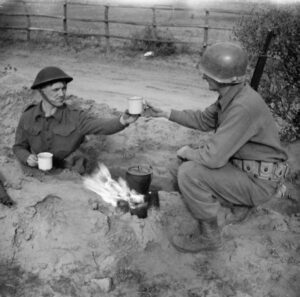 A British soldier with the 2/7th Middlesex Regiment shares a cup of tea with an American infantryman in the Anzio bridgehead, Feb. 10, 1944