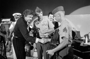 Johnny Cash receives an award from a Marine sergeant during his performance for military personnel at the naval station