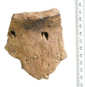 Fragment of a large round-shouldered, round-bottomed vessel with deep impressions widely spaced below the rim - the latter possibly created using the hoof of a dead roe deer faun. Residues found within suggest it was used to process meat stew (Mola)
