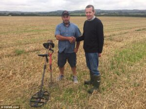 Mike Smale (left), 35, found the hoard of 600 rare ancient coins in a farmer's field in Bridport while hunting with friends from the Southern Detectorists club. He is pictured here with farmer Anthony Butler