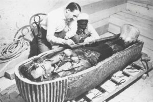 Archaeologist Howard Carter examining the third mummy-shaped sarcophagus, 1922, vintage photograph