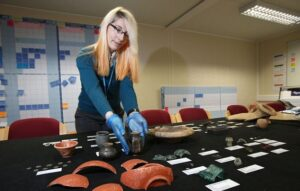 Archaeologists have unearthed a haul of more than 177,000 Roman artefacts under the A1 in Yorkshire. The discoveries have been described as 're-writing history'. Pictured is Dr Elizabeth Foulds a selection of the treasures