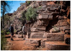 Two hikers gaze at the rock formations in Dales Gorge at Karijini National Park in Pilbara, western Australia.