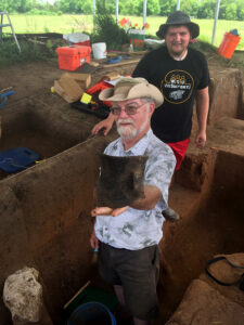 Professor Donald Blakeslee of Wichita State University shows a black pot unearthed by student Jeremiah Perkins, behind him.
